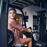 Shot of a young woman driving a forklift